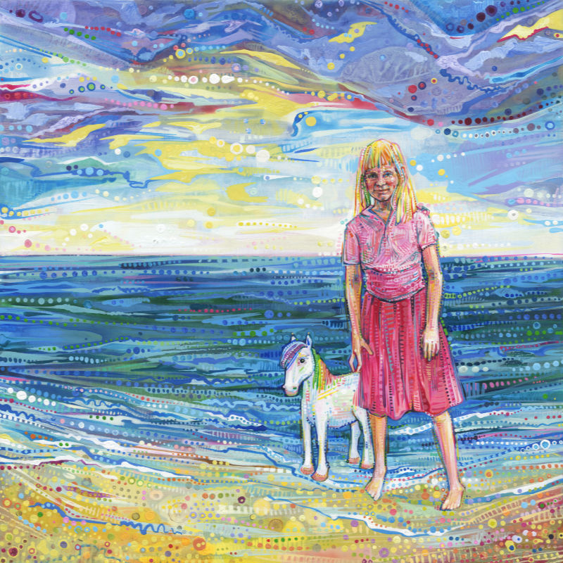 little blonde girl with a pony at the beach